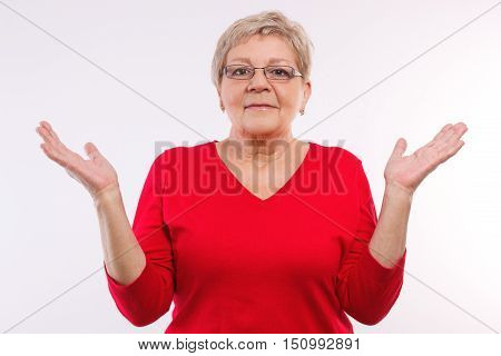 Happy smiling elderly senior woman throwing up her hands and shrugging shoulders human emotions and gesture having no clue