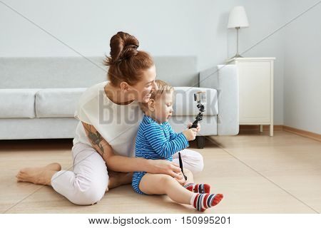 Sideways Portrait Of Happy Young Caucasian Mother And Son Sitting At The Floor At Home, Making Selfi