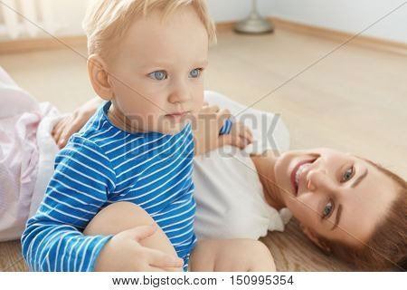 Positive Shot Of Blue-eyed Mother And Her Son Playing On The Floor Of Their Bedroom. Cute Toddler Si