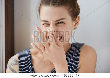 Close-up Shot Of Caucasian Girl Showing Disgust, Pinching Her Nose To Avoid Bad Smell. Brunette Girl