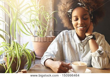 Young, Beautiful And Tender African Female Hipster Sitting At Home Table Near Windowsill With Two Bi