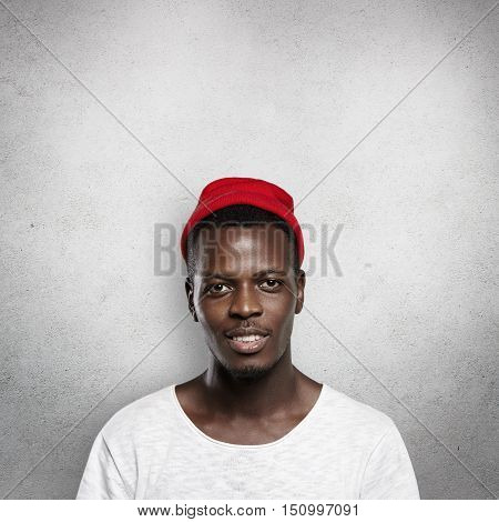 Style And Fashion. Good-looking Stylish African Man Wearing White T-shirt And Red Hipster Cap, Looki