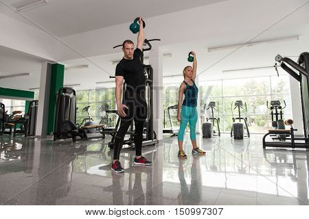 Man And Woman Kettle Bell Exercise