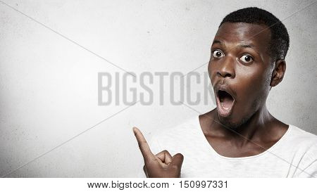 Look At That! Headshot Of Totally Shocked Bug-eyed African Man Dressed In White T-shirt, Opening His