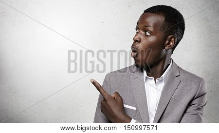 Advertising Concept. Headshot Of Surprised African Businessman Dressed In Gray Suit Looking With Ast