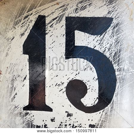 Old metal plate with the number fifteen close up