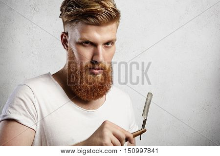 Young Caucasian Hipster-like Man In White T-shirt Trying To Decide Whether To Shave His Long Red-hai