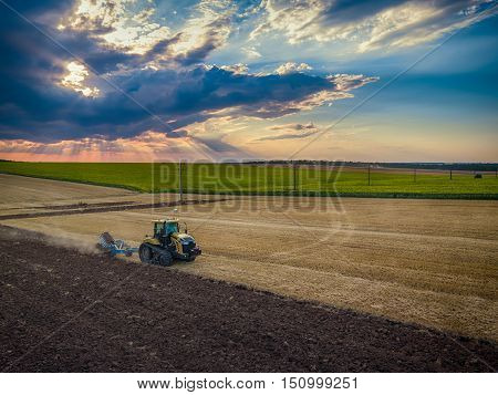 Tractor cultivating field at autumn aerial view