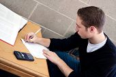 image of midterm  - A young high school or college student working on his math homework - JPG