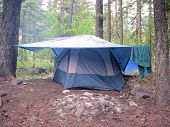 stock photo of tarp  - a tent sits under a tarp at camp sure to stay extra dry - JPG