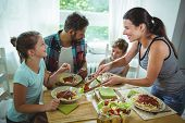 Smiling woman serving meal to her family at home poster