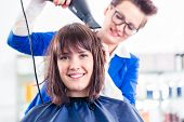 Female coiffeur blow dry women hair with blow dryer in shop poster