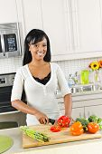 image of healthy food  - Smiling black woman cutting vegetables in modern kitchen interior - JPG
