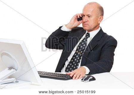 businessman sitting at desk in office and talking on mobile phone