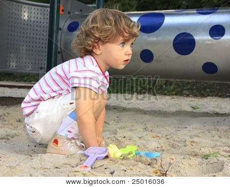 The little child playing in the sandbox