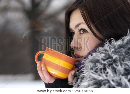 Young woman having a hot drink in winter open air.