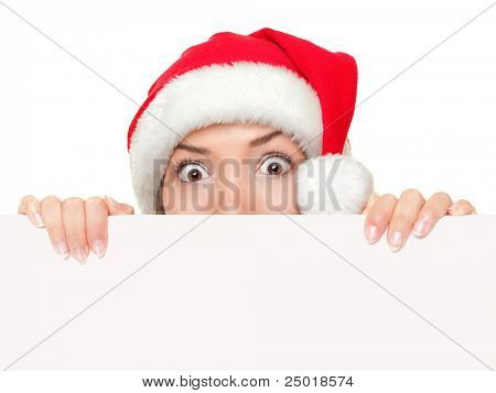 Christmas sign woman peeking over empty blank paper sign wearing santa hat isolated on white background. Funny surprised and shocked look on santa girl face.