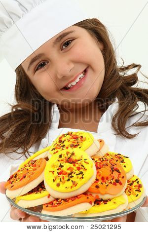 Adorable Girl Child In Chef Uniform With Iced Thanks Giving Day Cookies.