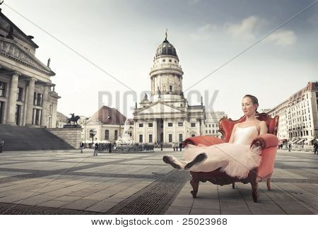 Beautiful ballerina resting on an armchair with museum in the background