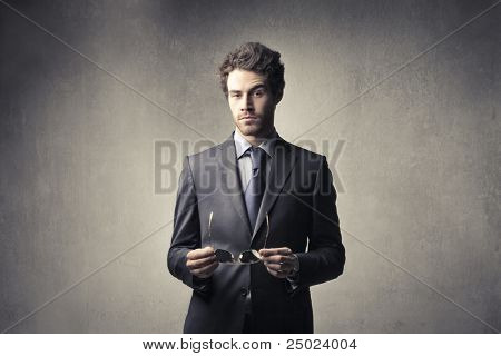 Handsome businessman holding eyeglasses
