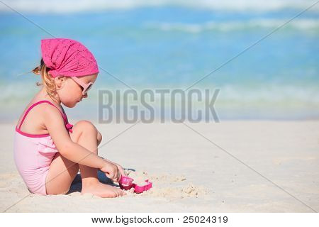 Adorable little girl playing with toys at tropical beach