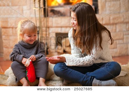 Two girls sitting fireside and opening christmas presents
