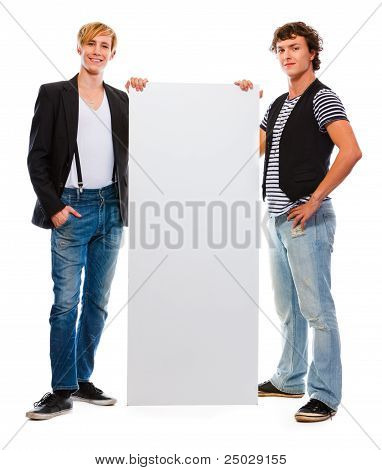 Two Modern Teenagers Holding Blank Billboard. Isolated On White