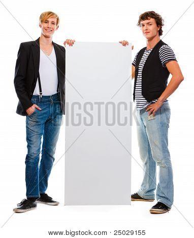 zwei moderne Teenager holding blank Billboard. isoliert auf weiss
