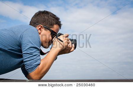 Handsome young professional photographer taking photos against blue sky