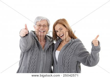 Mature mother and attractive daughter hugging each other, showing thumb up, smiling happily in identical cardigans.?