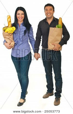 Full Length Of Couple Carrying Bags With Food