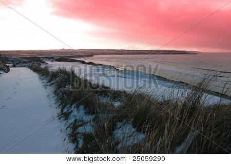 Coastal Snow Covered Links Golf Course With Red Sunset