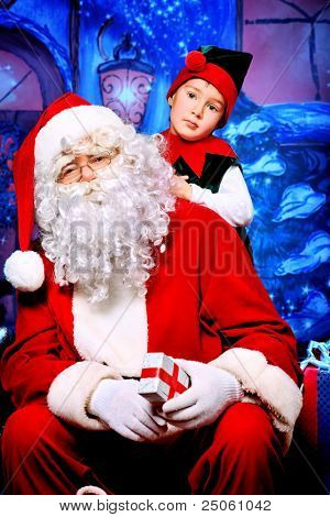 Santa Claus sitting with a little cute boy elf over Christmas background.