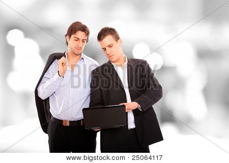 Closeup of two standing looking at a notebook computer in a light and mordern business environement