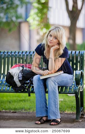 Portrait of young female student sitting on bench at college campus