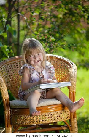 Little girl reading book sitting in wicker chair outdoor in summer day