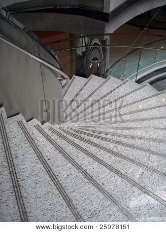 A spiral marble like staircase with chrome handle bar.