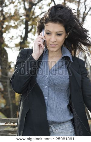 Businesswoman In A Park Talking Mobile Phone.