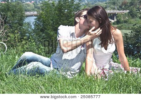Beautiful Man And The Woman Kiss Ashore At The River In The Sunny Day  Against A Green Grass And The
