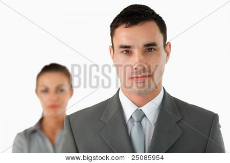 Close up of serious looking businessman with colleague behind him against a white background