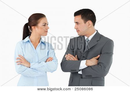 Serious business partners with arms folded looking at each other against a white background