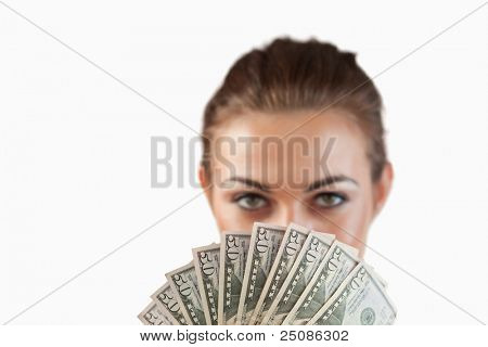 Close up of bank notes being held by businesswoman against a white background