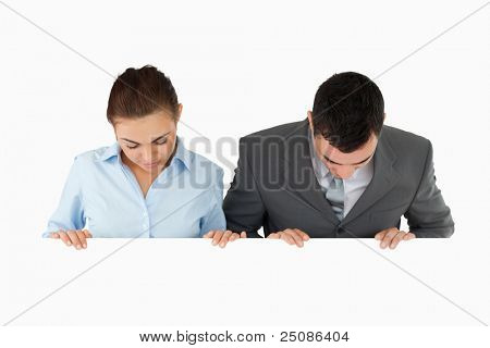 Business partners looking down at sign they are holding against a white background