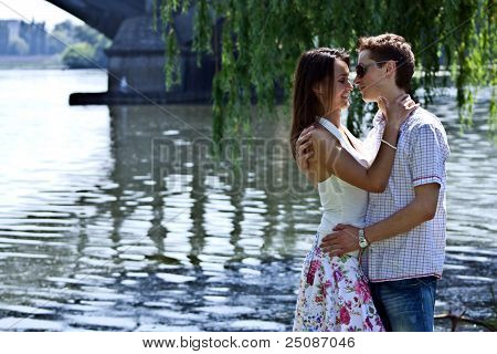 The Man And The Woman Kiss Ashore At Against The Bridge