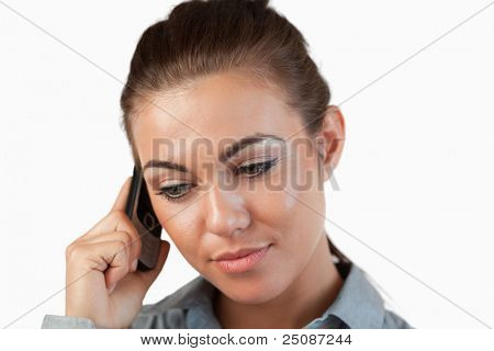 Close up of businesswoman listening closely to caller against a white background