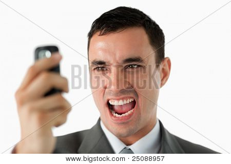 Close up of businessman upset about text message against a white background