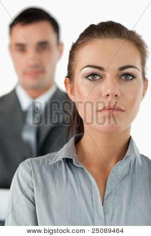 Close up of serious looking businesswoman with colleague behind her against a white background