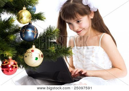 Little Smiling Girl Looks At Her Laptop Computer
