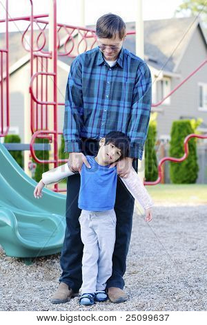 Father Helping Disabled Son At Playground