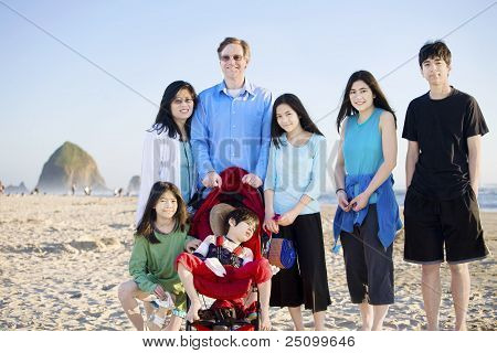 Large Family Of Seven Standing On The Beach By The Ocean